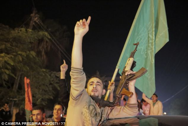 A Palestinian man holds his gun in the air as he celebrates the ceasefire in Gaza City
