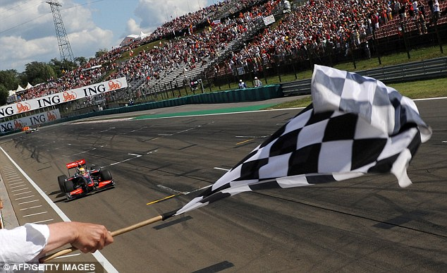 Winner: The British star takes the chequered flag for the first time in 2009