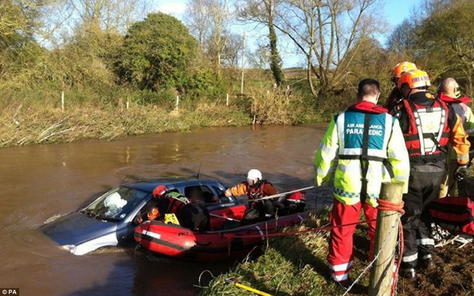 River rescue from the water: Three elderly people being assisted from their car after it was swept away as they drove into a ford in Warwickshire