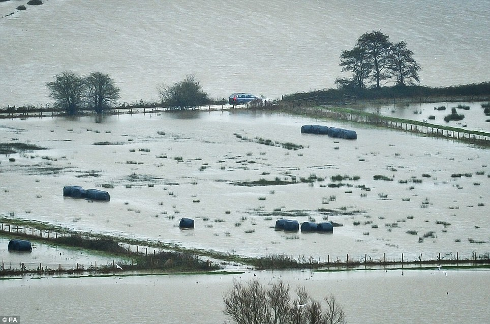 No access: A car struggles along a road on the Somerset Levels where continuous heavy rain has caused severe flooding