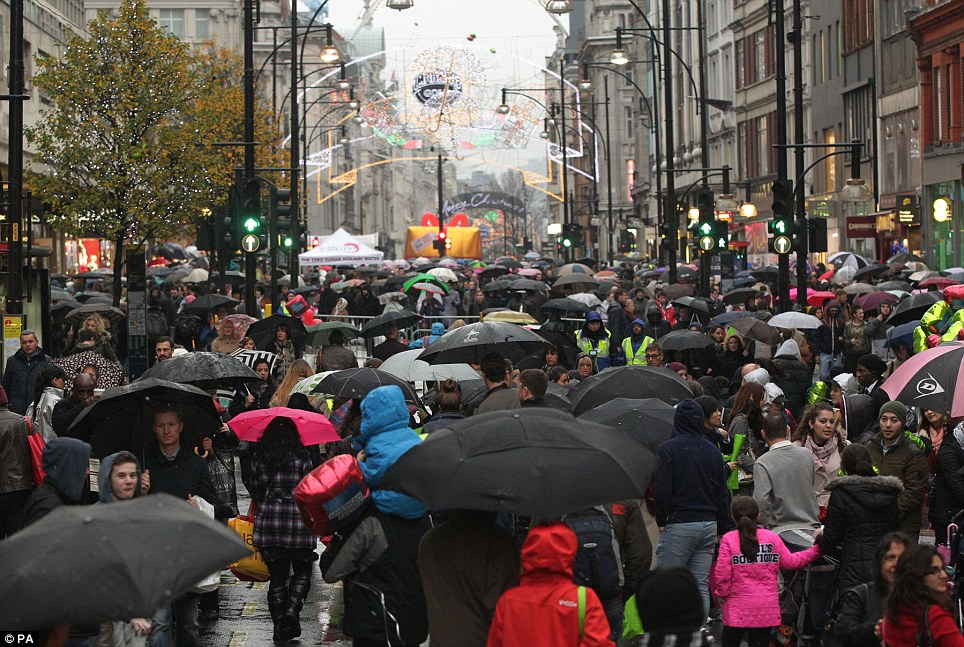 The shop goes on: A sea of umbrellas on London's Oxford Street on a day when both it and neighbouring Regent Street were shut off to traffic