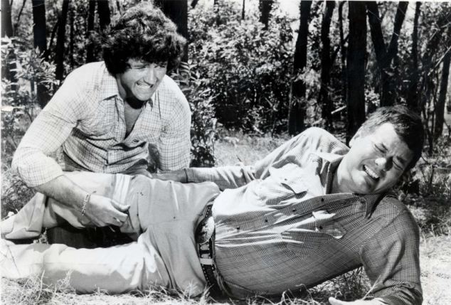 Classic: In a scene from Dallas, J.R. Ewing (Larry Hagman, foreground) is wounded by a sniper and receives aid from Bobby Ewing (Patrick Duffy)