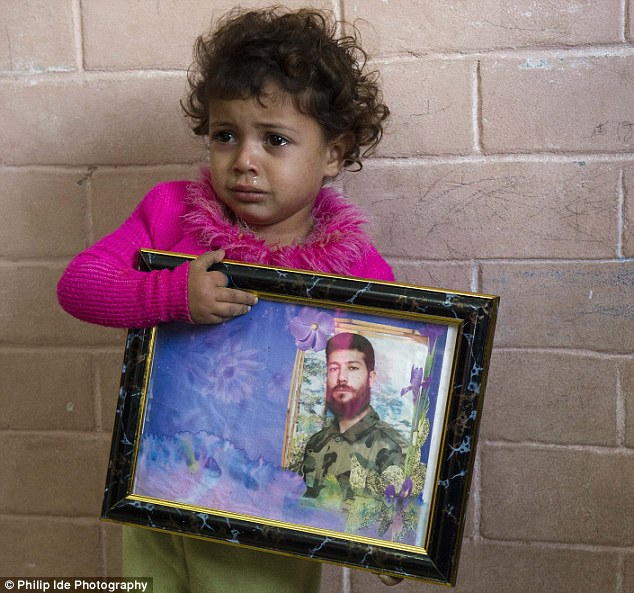 Tearful and terrified: Three--year-old Baraa (whose name means Innocence), clutches a picture of her father who was publicly executed and dragged through streets of Gaza by a motorcycle lynch mob