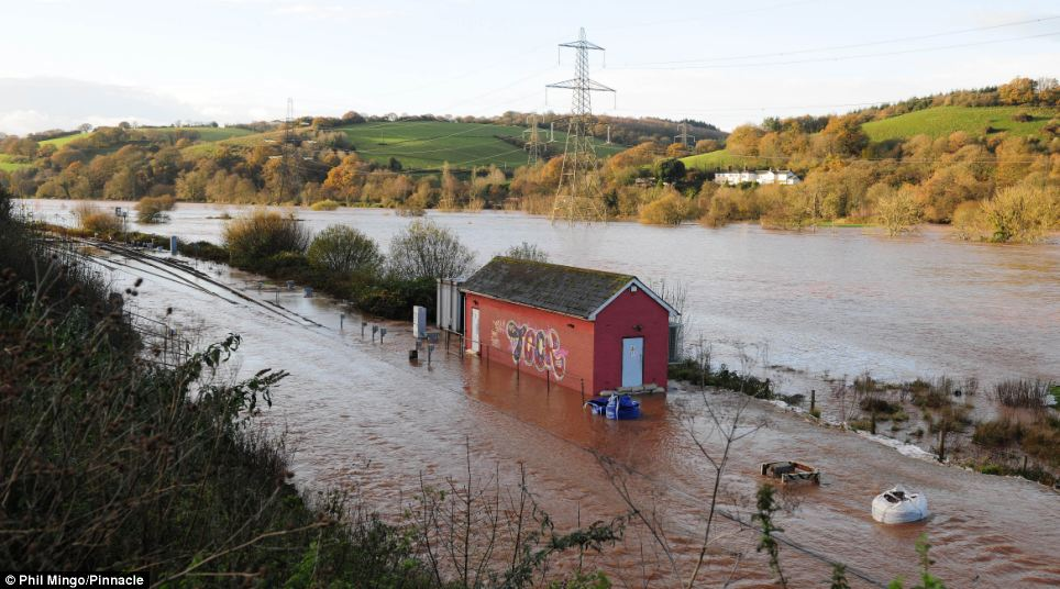 Some major train services have been severely disrupted as a result of flooding on the tracks running along the River Exe. Pictured is Cowley Bridge where the river burst its banks for the second time