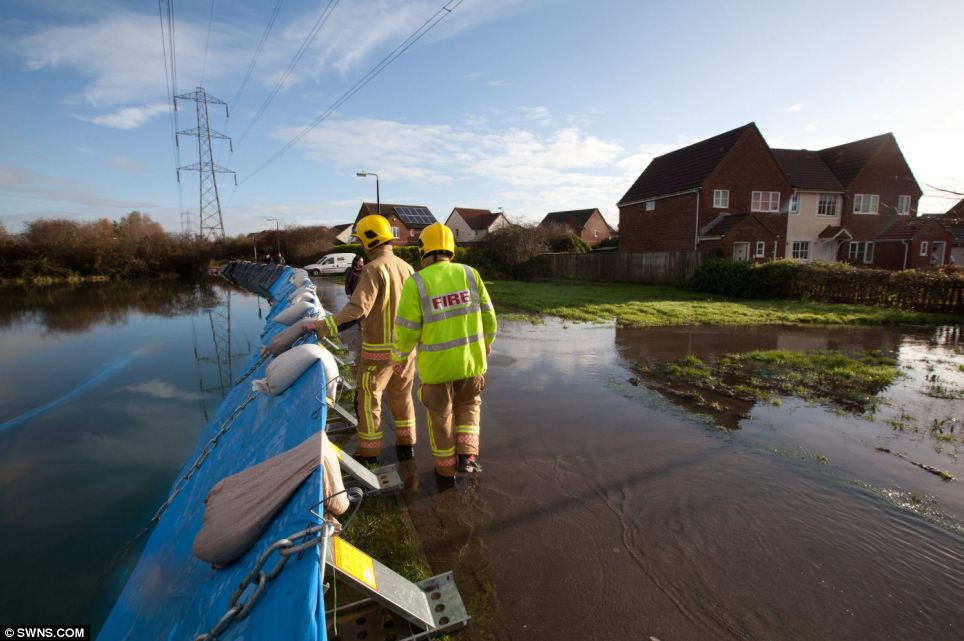 Firefighters inspect flood barriers which were breached by flood water after flash flooding in Worle, Somerset, over the weekend