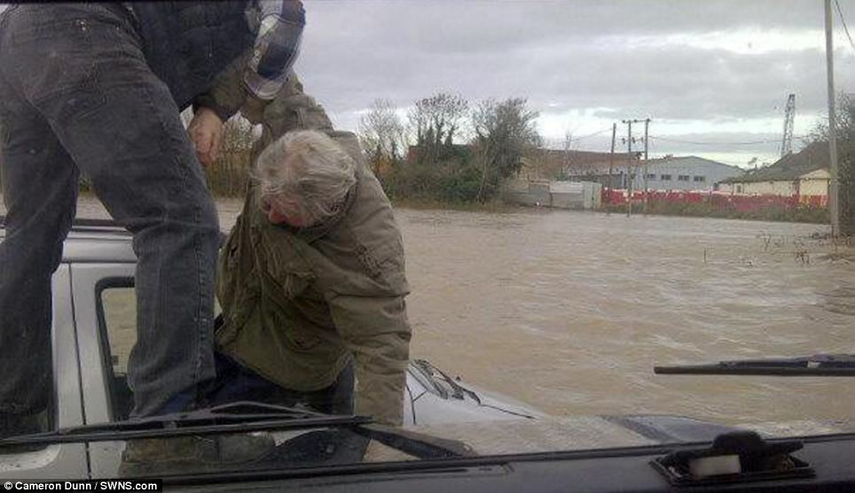 David Dunn and his son, Cameron, were able to drive through the water to help the stranded pensioner out of his car and onto the bonnet of their Land Rover in Keynsham, Somerset