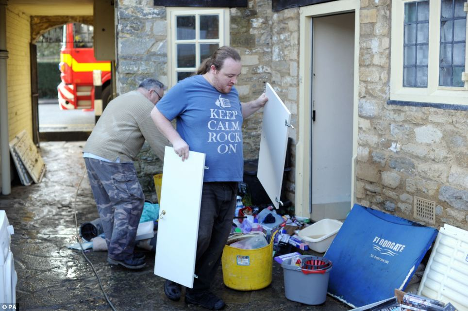 A man's T-shirt sums up the mood in Malmesbury as he clears out damaged property from a house in the town