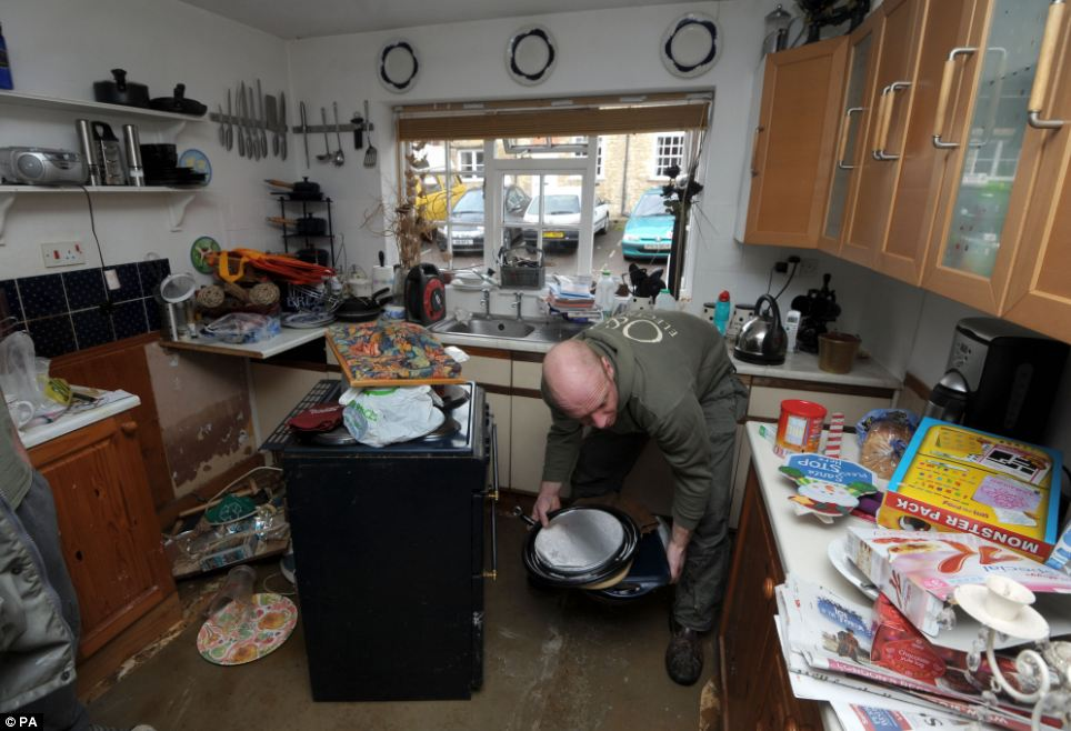 A man helps clear his mother's house in Malmesbury and tries to salvage what he can after the floods hit her home