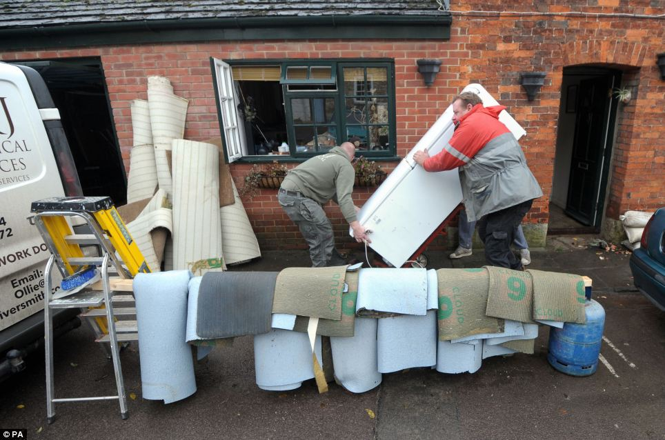Oliver Smith helps to remove carpets and a fridge freezer from his mother's home in Malmesbury after it was flooded over the weekend