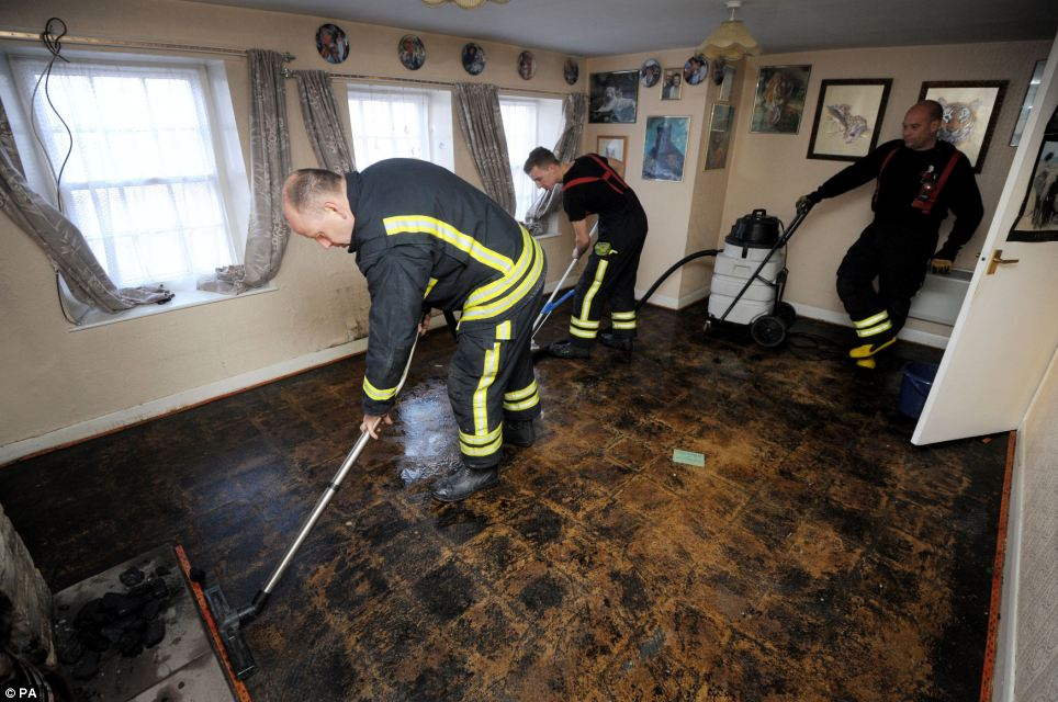 Wiltshire Fire and Rescue firefighters use an Aquavac to help clean the floors of a house in Malmesbury that was flooded