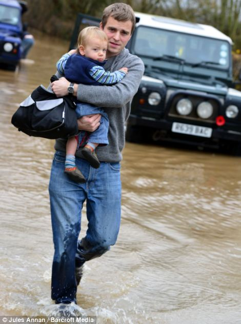 Joe Waller makes his way through flood waters with his son after becoming marooned when their car broke down