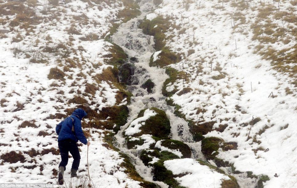 A walker negotiates a brook amid snowy scenes on the northern Pennines today