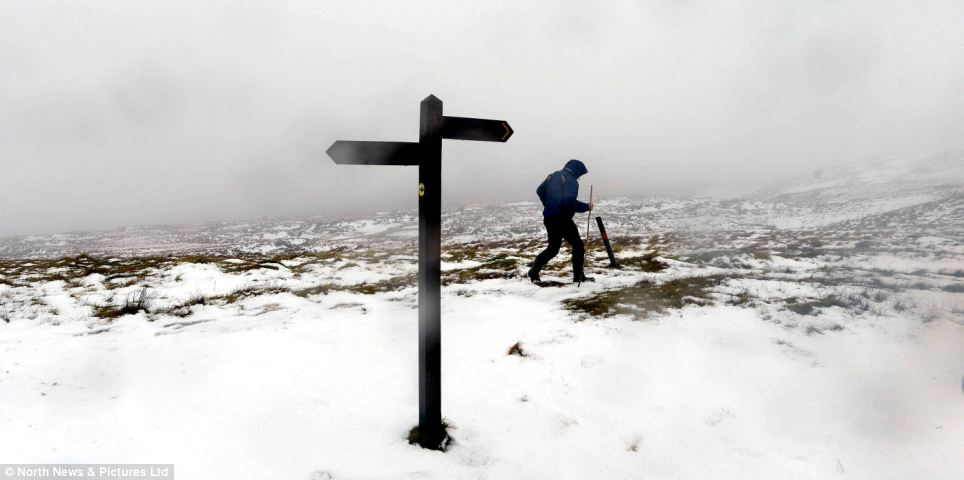 A walker endures cold weather on top of the Pennines today as he battles through the fog, wind and snow