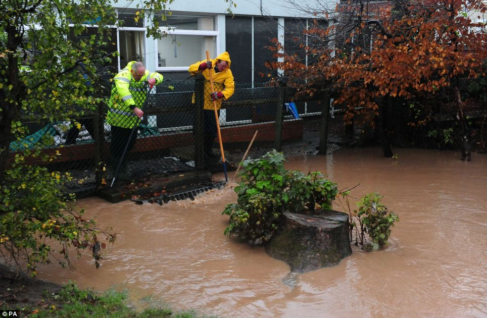 Two men work to keep a drain clear behind the Friarage Hospital in North Allerton, North Yorkshire during last month's flooding