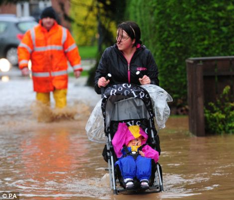 A woman pushes a child in a pushchair through flood water in Northallerton, North Yorkshire as as the heavy rain continues across the UK