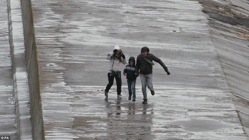 A family battles against the strong winds and rain as floods hit Dublin today causing chaos across the region