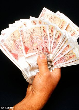 A hand holding £50 notes