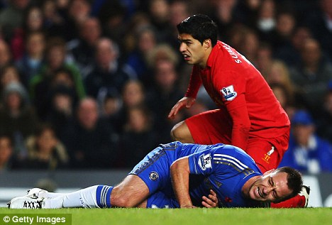 Nasty: Terry's injury looked serious after an accidental collision with Liverpool's Luis Suarez (top)