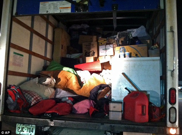 Mess on wheels: The back of the truck was piled with the family's belongings, boxes, sleeping bags, appliances and a gas can