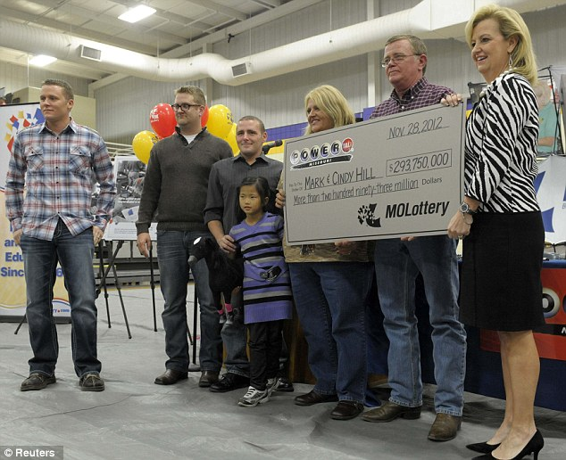 Top prize: The Hill family holds a check presented by Missouri Lottery director May Scheve (right). Left to right ,sons Jason, Cody, Jarod, adopted daughter Jaiden, and ticket holders Cindy and Mark Hill