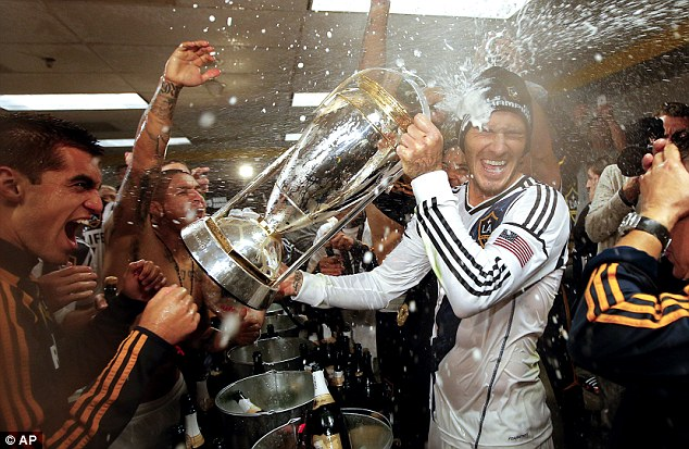 Party time: Beckham and his tam-mates begin the celebrations