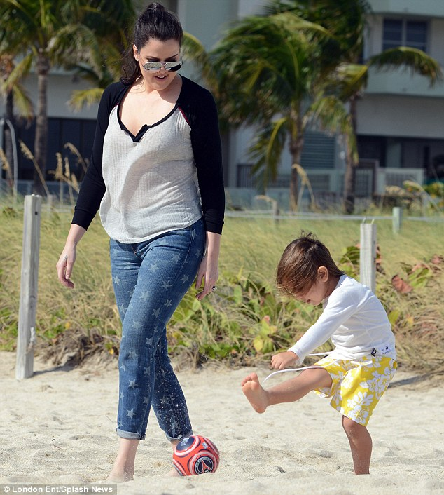 Keep your eye on the ball: Khloe coaches Mason through some soccer moves on the beach