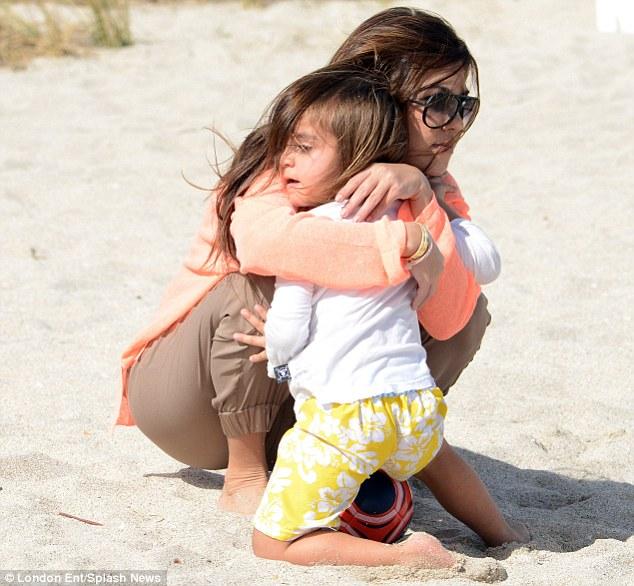 Hugging it out: Kourtney envelops the cute youngster in a motherly embrace