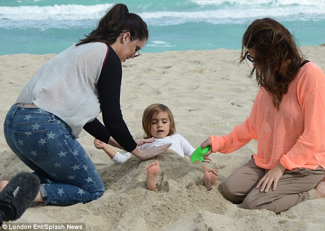 Fun in the sun: Kourtney and Khloe buried little Mason in sand on the beach during a day out in Miami on Sunday