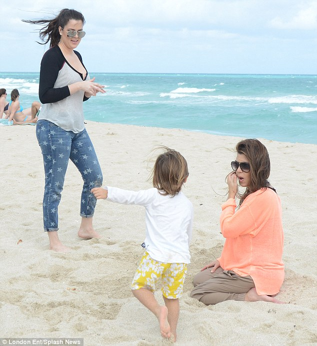 Family frolics: Little Mason appears to be directing his mother and Auntie Khloe as they enjoyed a beach day together