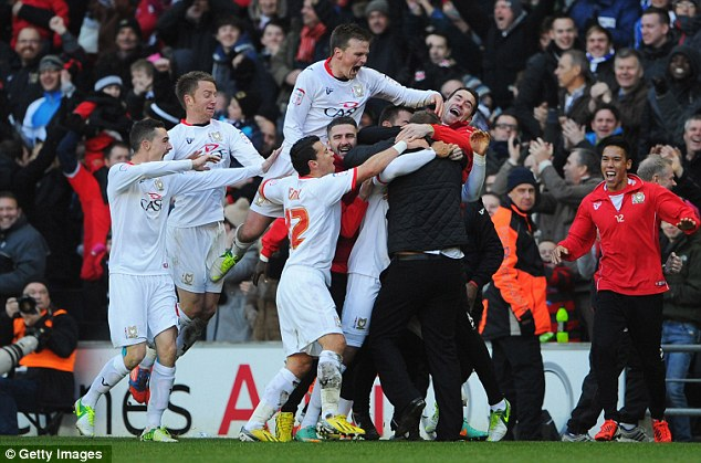 Mobbed: MK Dons celebrate their last-gasp winner which dumped AFC Wimbledon out of the FA Cup
