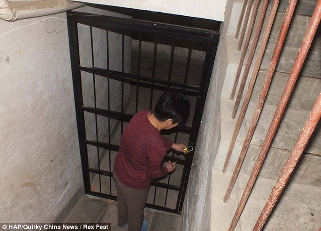 A resident unlocks the heavy metal door which led to the underground dungeon where Li Hao kept the six women for up to 21 months
