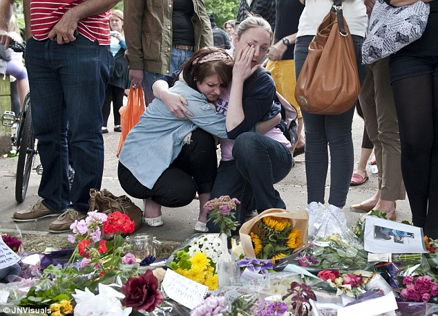 An unofficial shrine: Two fans of singer Amy Winehouse console each other outside the singer's Camden home shortly after her death last year