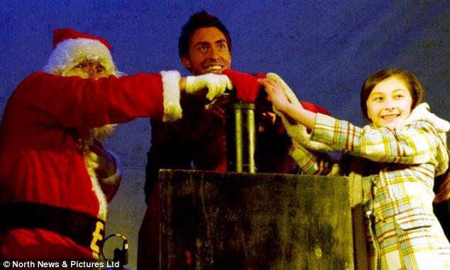 Ross Adams (centre) alongside Santa Claus and a volunteer lighting up Stanley Christmas tree