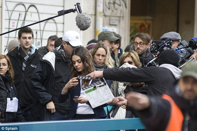 Lost in the crowd: A crew member marks a new scene while Mila prepares to film