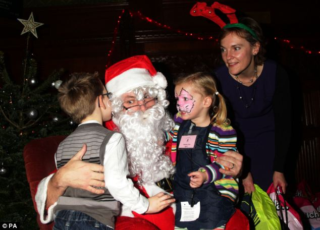 Gifts: Ed Balls dressed as Santa with Ed Miliband's wife Justine Thornton as he handed out presents to children