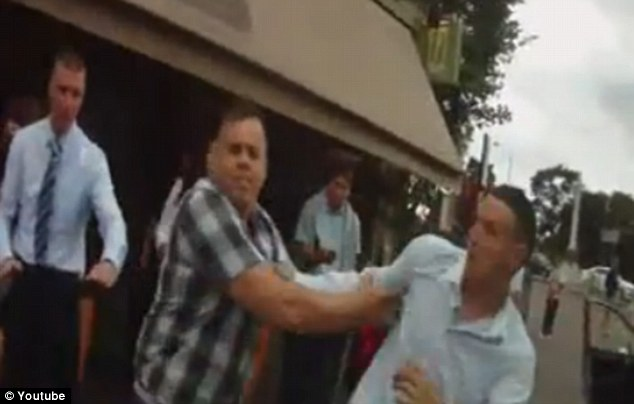 Street fight: Driver John Nicholls, right, was charged with assault - but escaped with a fine