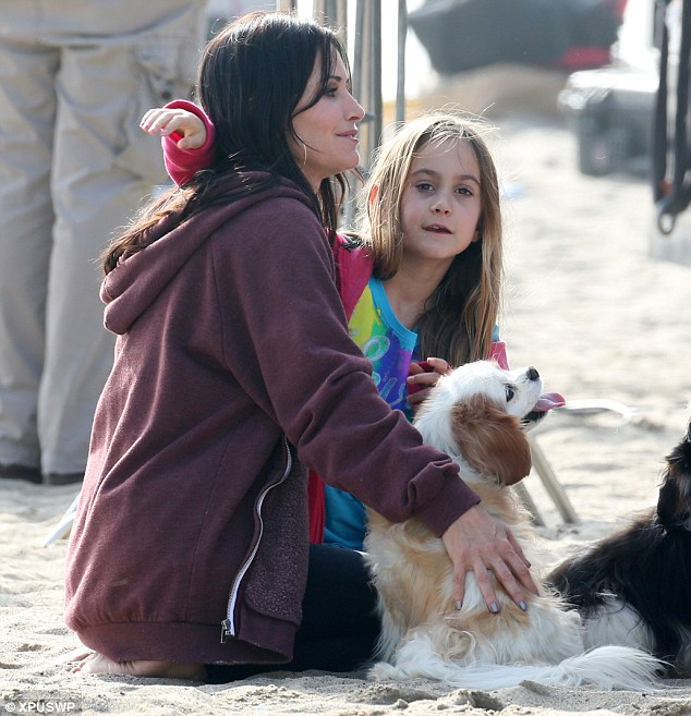 Family time: Coco and Courtney are joined by an adorable little dog as they sit in the sand at a Santa Monica beach