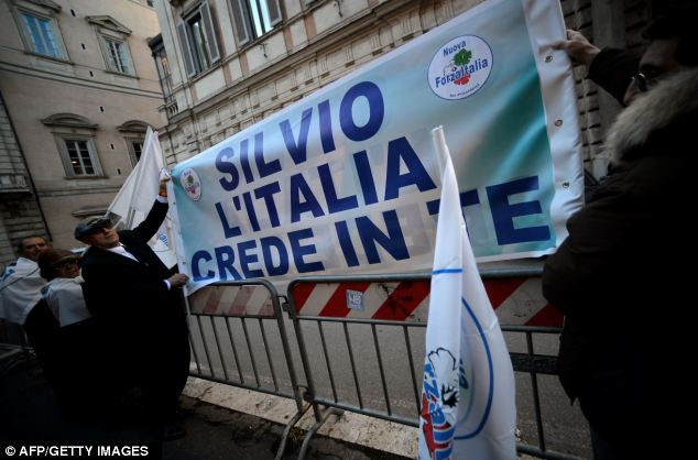 Supporters of fromer Italian Prime Minister Silvio Berlusconi hold a banner reading 'Silvio, Italy believes in you' in front of Berlusconi's Roman residence on Thursday