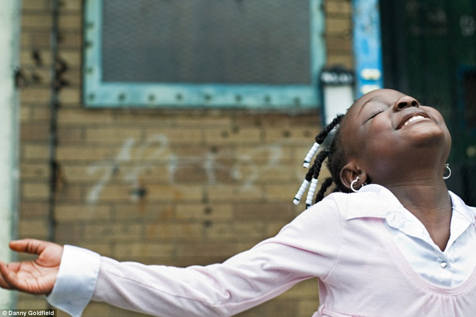 Home sweet home: This young girl from Angola takes in the New York air outside her home