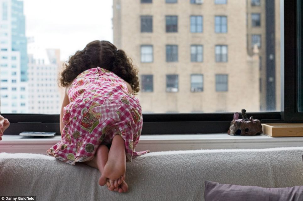 American dreaming: Rhianna peers out of a highrise window while Celeste's hand creeps into the frame, left. The girls are both from the United Kingdom