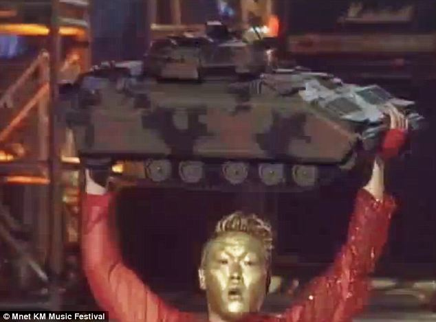 Psy, with his face painted gold, posed with a model of an camouflaged tank during the 2002 anti-war demonstrations in Seoul