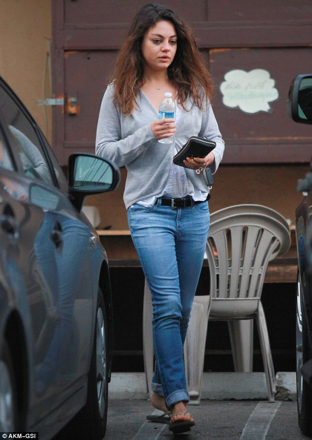 Fresh faced: Mila wore her hair down as she stepped out in a pair of flip flops, jeans, white top and grey cardigan