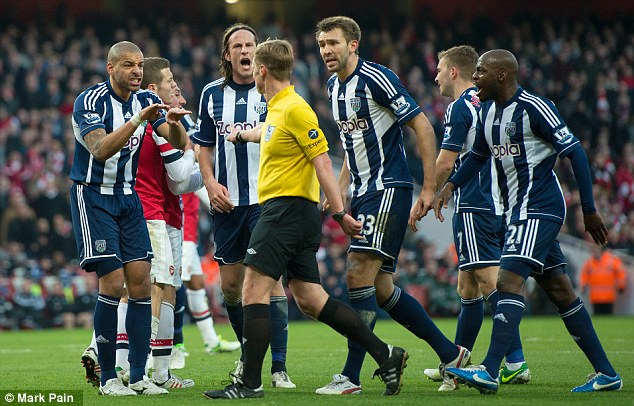 Bust up: Mike Jones is surrounded by West Brom players after awarding the first penalty