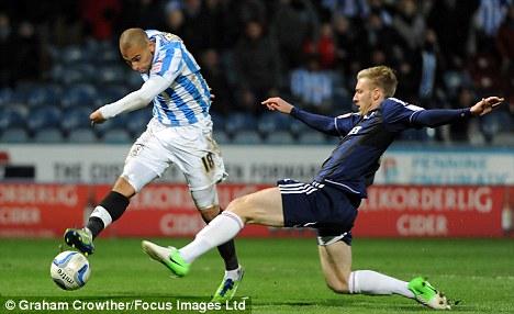 Last-gasp: James Vaughan fires the equaliser for Huddersfield