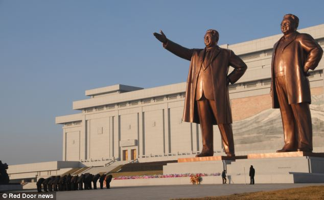 Gigantic follies: North Koreans bow before statues of Kim Il-song and Kim Jong-il near the Ryugyong Hotel in Pyongyang