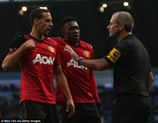 Firm hand: Referee Martin Atkinson talks to United's Rio Ferdinand (left) and Danny Welbeck
