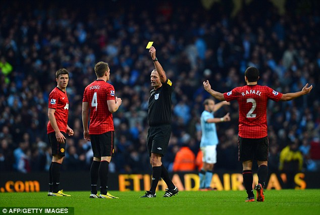 Booked! Atkinson flashes a yellow card at United's Phil Jones