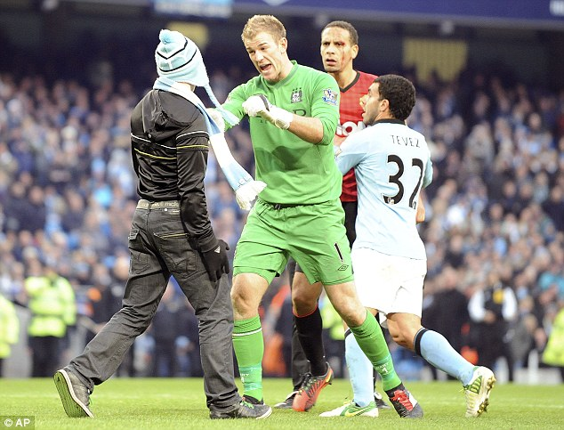 Pitch invader: A Manchester City fan was able to get too close to the players during Sunday's derby
