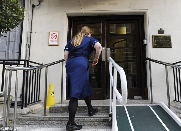 Carrying on: An unidentified nurse  enters King Edward VII Hospital in Marylebone, central London