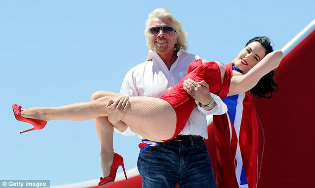 Scrap in the skies: Virgin Atlantic was created in the 1980s to take on British Airways' dominance of long-haul flights; Branson has not been shy of the occasional photo shoot to promote the brand - seen here with Dita Von Teese in 2001